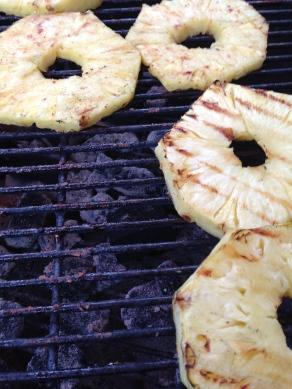 Grill de ananas direct boven de kolen op de BBQ