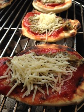 Leg de pizza's terug op de grill direct boven de kolen om de 'ongebakken' zijde af te bakken