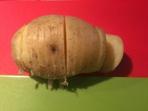 Snijd de aardappel in dunne schijfje, maar snijd niet helemaal door!